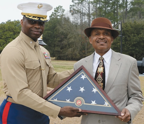 Lt. Col. George Lampkin, operations officer, C4, Marine Corps Logistics Command, presents Bennie Paige an American flag during his retirement ceremony held in front of Building 3700, Feb. 20. Paige retired after 37 years of service and the flag was flown in his honor.