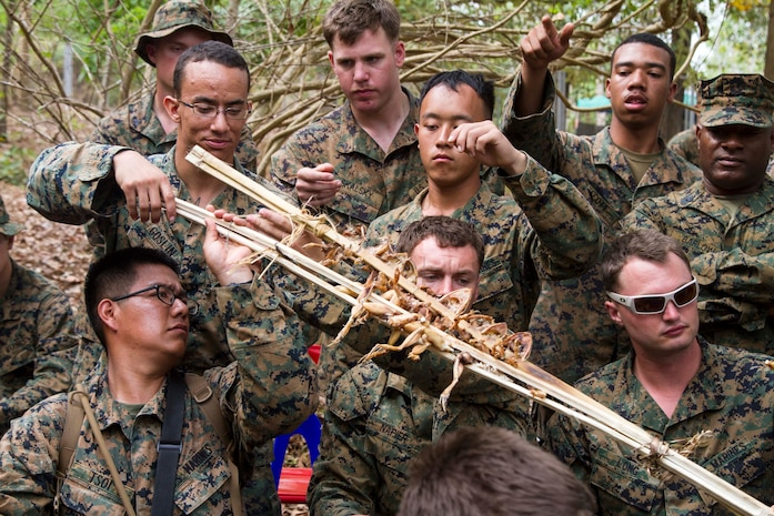 BAN CHAN KREM, Kingdom of Thailand – Marines pass along a piece of bamboo holding cooked frogs during a jungle survival class Feb. 14 at Ban Chan Krem, Kingdom of Thailand during Exercise Cobra Gold. The jungle survival class teaches U.S. Marines basic survival skills that can be used in environments similar to the jungles of Thailand. The course includes knowledge on edible vegetation, water collection, and venomous animal handling. The Marines are with 3rd Battalion, 1st Marine Regiment currently assigned to 3rd Marine Division, III Marine Expeditionary Force under the unit deployment program. (U.S. Marine photo by Lance Cpl. Stephen D. Himes/Released)