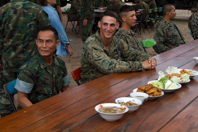Royal Thai and U.S. Marines wait to begin dinner Feb. 17 at Ban Chan Krem, Kingdom of Thailand during Exercise Cobra Gold. Cobra Gold is designed to advance regional security and ensure effective response to regional crises by exercising a robust multinational force from nations sharing common goals and security commitments in the Asia-Pacific Region. The Thai Marines are with 3rd Company, 7th Battalion with the Royal Thai Marine Corps. The U.S. Marines are with 3rd Battalion, 1st Marine Regiment currently assigned to 4th Marine Regiment, 3rd Marine Division, III Marine Expeditionary Force under the unit deployment program.
