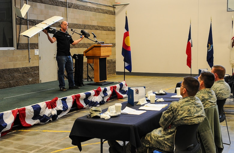 Chris Miser, Falcon UAV principal, explains the uses of unmanned aerial vehicle at the monthly Aurora Defense Council meeting Feb. 27, 2014, at the Navy Operational Support Center Denver facility on Buckley Air Force Base, Colo.  The meeting included a briefing from base partner commanders, local and state organizations, and an UAV demonstration by Falcon UAV. (U.S. Air Force photo by Senior Airman Phillip Houk/Released)