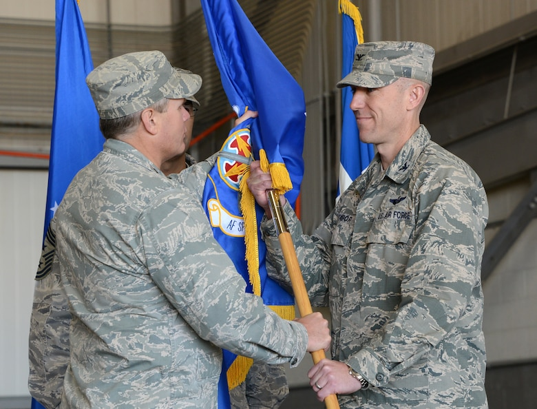 Lt. Gen. Eric Fiel, Air Force Special Operations Command commander, and Col. David Tabor pass the symbolic flag giving Tabor command of the Air Force Special Operations Air Warfare Center during a ceremony at Duke Field, Fla., Feb. 27, 2014. Tabor took command of AFSOAWC which is responsible for doctrine development, education, training, and execution of the command's irregular warfare capabilities. (U.S. Air Force photo by Master Sgt. Steven Pearsall)