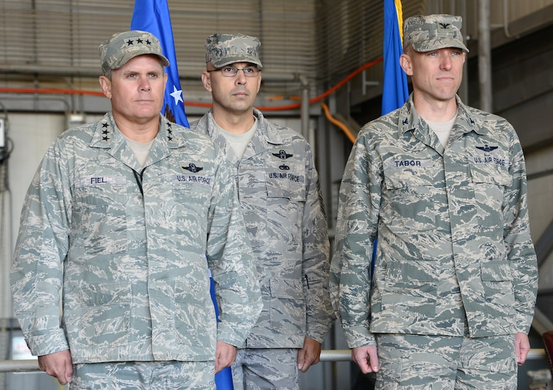Lt. Gen. Eric Fiel, Air Force Special Operations Command commander, and Col. David Tabor stand at attention for the symbolic passing of the flag held by Command Chief Master Sgt. Michael Klausutis, giving Tabor command of the Air Force Special Operations Air Warfare Center at a ceremony at Duke Field, Fla., Feb. 27, 2014. Tabor took command of AFSOAWC which is responsible for doctrine development, education, training and execution of the command's irregular warfare capabilities. (U.S. Air Force photo by Master Sgt. Steven Pearsall)