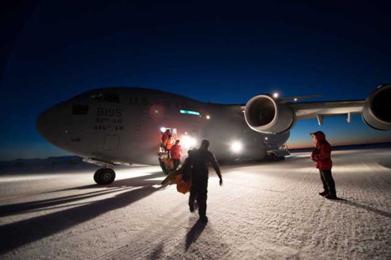 U.S. Antarctic Program participants exit a McChord C-17 at Pegasus Airfield on Aug. 15. The flight carried 51 people to McMurdo Station, which has been in winter isolation for months.  (Courtesy photo by Alasdair Turner)