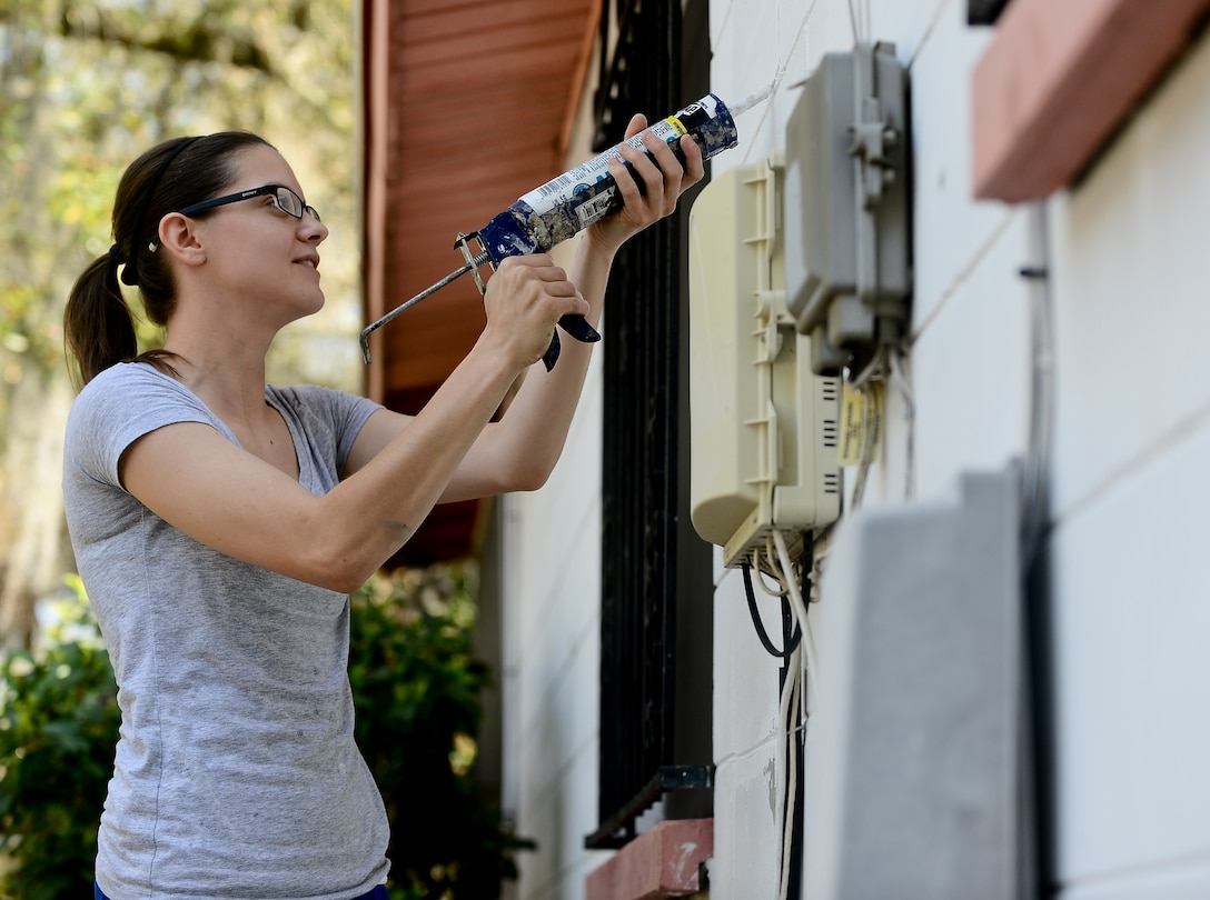 Staff Sgt. Alyssa Rade, 6th Security Forces Squadron marine patrolman, uses caulk to repair cracks on the side of a house during a Habitat for Humanity volunteer opportunity Feb. 25, 2014, in Tampa, Fla. The project beautified the exterior of two homes in the local Tampa community. (U.S. Air Force photo by Senior Airman Melanie Bulow-Gonterman/Released)