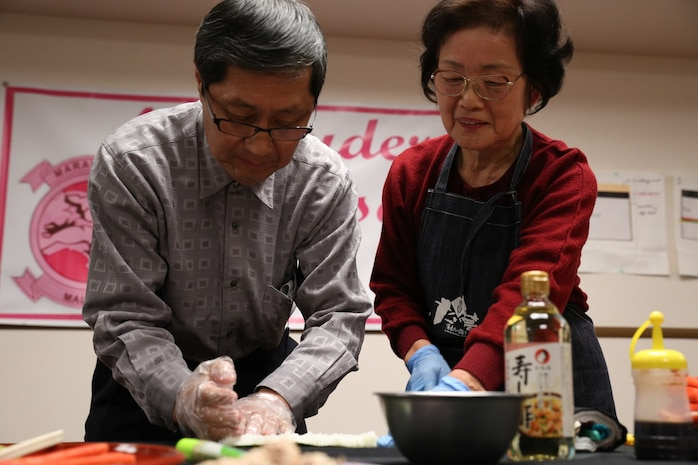 Keijiro Akiyama, owner of Akiyama Sushi, and Michiyo Okazaki, a Japanese volunteer, demonstrate how to make Norimaki during a sushi making class hosted by the Marauders Spouse Club, Feb. 22, 2014, aboard Marine Corps Air Station Iwakuni, Japan. The Marauders Spouse Club is one of the longest lasting spouse clubs aboard station.