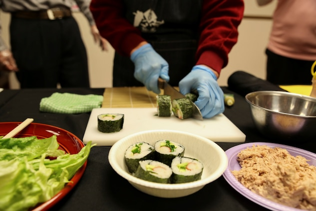 Michiyo Okazaki, a Japanese volunteer, demonstrates how to make Norimaki during a sushi making class hosted by the Marauders Spouse Club, Feb. 22, 2014, aboard Marine Corps Air Station Iwakuni, Japan. The Marauders Spouse Club has found that events involving the Japanese culture are the most popular among the spouses.