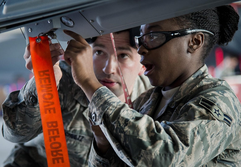 Airman 1st Class Quionjay Jackson and Senior Airman Thomas Schultz discuss the next procedure to accomplish on their F-16 Fighting Falcon during the annual weapons load crew of the year competition Feb. 14, 2014, at Eglin Air Force Base, Fla. (U.S. Air Force photo/Samuel King Jr.)