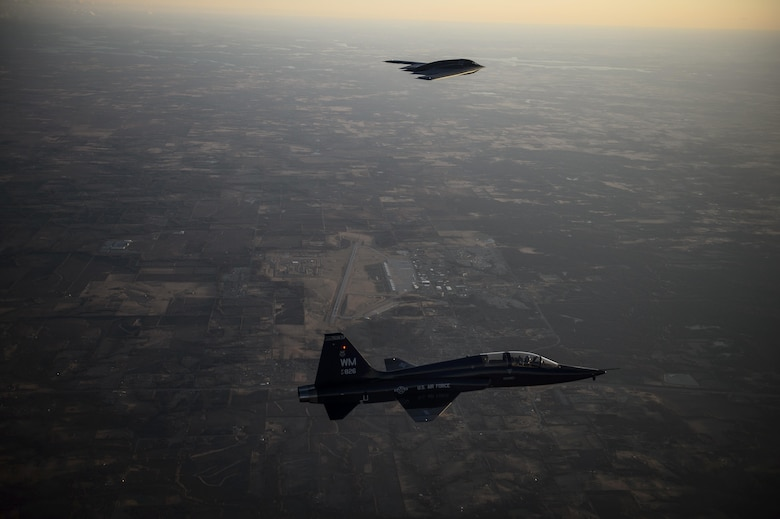 A T-38 Talon flies in formation with a B-2 Spirit during a training mission Feb. 20, 2014, over Whiteman Air Force Base, Mo. The B-2 is a multirole bomber capable of delivering both conventional and nuclear munitions. (U.S. Air Force photo/Staff Sgt. Jonathan Snyder)