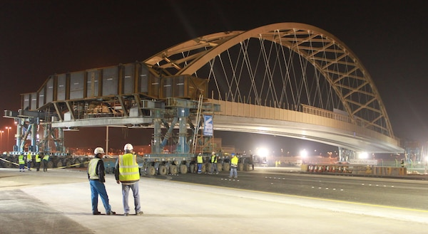 A tied arch bridge, known as the flyover bridge, was moved into place over the Khalifa Bin Salman Causeway connecting Naval Support Activity (NSA) Bahrain to the U.S. Navy port facility (NSA II). The 122.5 meter long, 21.4 meter high, 2650 metric ton bridge was constructed on NSA II, and will be driven across the causeway on self-propelled modular trailers (SPMT), and set in place on pre-constructed abutments. The greatest benefit of this process allows Bahrain traffic to be disrupted for hours as opposed to months it would have taken to build the bridge in place. The bridge move was a first of its kind for the Middle East District