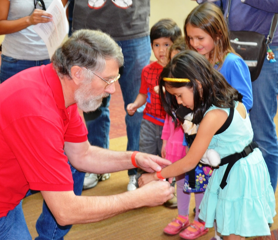 ALBUQUERQUE, N.M., --Greg Everhart, district archeologist, assisted a young participant with her wristband during the S.T.E.M Festival events, Feb. 22, 2014.