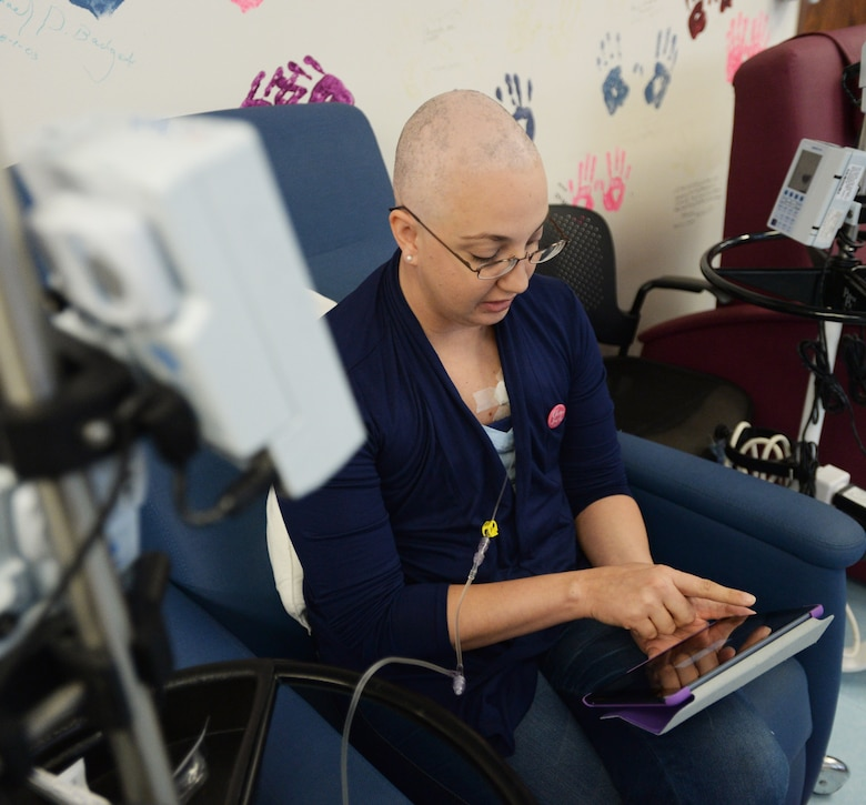 Staff Sgt. Amanda Dick, 15th Medical Support Squadron patient flight, reads an eBook during her chemotherapy treatment at Tripler Army Medical Center, Honolulu, Hawaii, Feb. 26, 2014. Since being diagnosed with breast cancer in October 2013, Dick has finished one-of-two rounds of chemotherapy, and is expected to be done with treatment in April. (U.S. Air Force photo/Staff Sgt. Alexander Martinez)