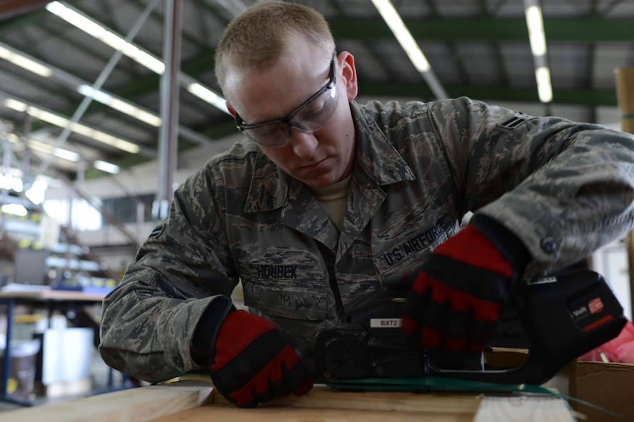 U.S. Air Force Airman 1st Class Frank Houdek, 52nd Logistics Readiness Squadron packing and crating specialist from Tucson, Ariz., secures a crate with metal bands at Spangdahlem Air Base, Germany, Feb. 25, 2014. Traffic Management Office Airmen complete the banding process to ensure the crate will not fall apart during shipping. (U.S. Air Force photo by Senior Airman Gustavo Castillo/Released)