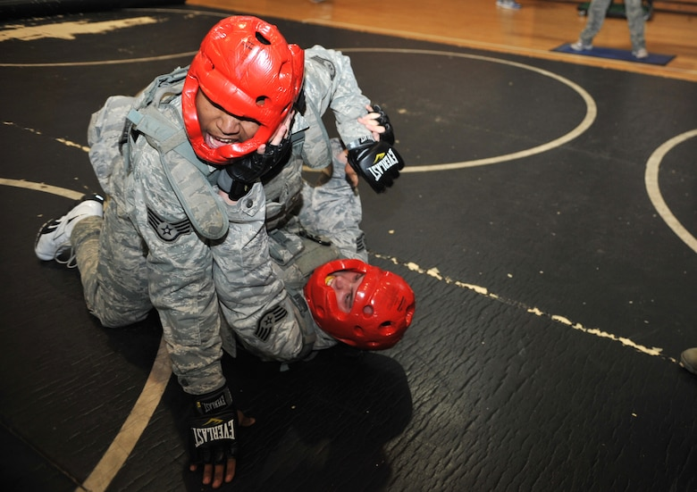 "Airmen from the 51st Security Forces Squadron engage in combatives training during a House of Pain exercise in the fitness center at Osan Air Base, Republic of Korea, Feb. 27, 2104. Other events in the confidence course included sprints, box jumps and ""Spiderman"" push-ups, each lasting for 90 seconds. (U.S. Air Force photo/Airman 1st Class Ashley J. Thum)"