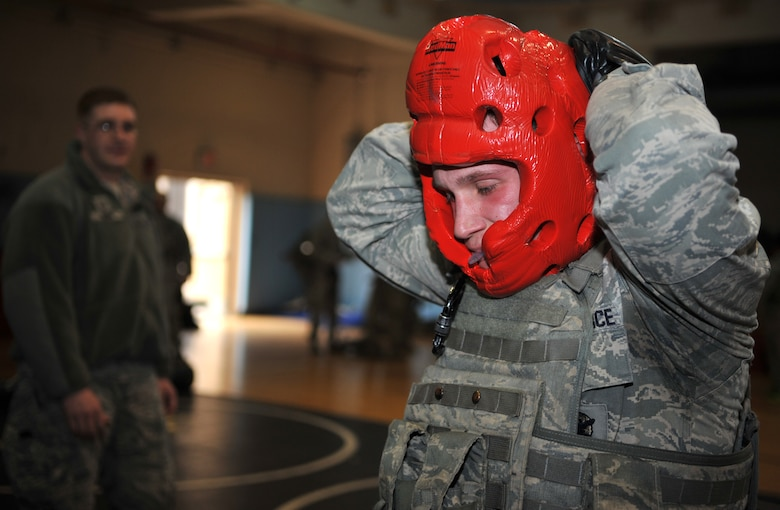 A member of the 51st Security Forces Squadron secures his protective headgear prior to a combatives bout during a House of Pain training event in the fitness center at Osan Air Base, Republic of Korea, Feb. 27, 2014. The confidence course featured several different stations that defenders rotated between every 90 seconds. (U.S. Air Force photo/Airman 1st Class Ashley J. Thum)