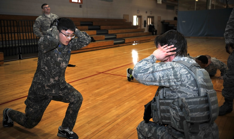A member of the Republic of Korea air force air police completes jumping lunges with encouragement from a member of the 51st Security Forces Squadron during a House of Pain training event in the fitness center at Osan Air Base, ROK, Feb. 27, 2014. Defenders frequently train with their ROK counterparts to strengthen the relationship between the services. (U.S. Air Force photo/Airman 1st Class Ashley J. Thum)