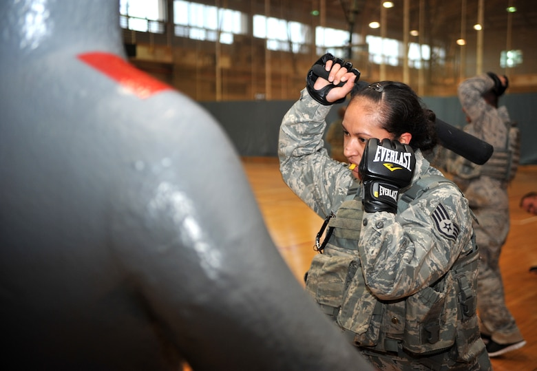 "A defender from the 51st Security Forces Squadron wields a night stick prior to striking a rubber mannequin during a House of Pain training event in the fitness center at Osan Air Base, Republic of Korea, Feb. 27, 2014. Airmen were required to repeatedly strike the figure while shouting ""get back,"" to practice techniques they would use if they were attacked on duty. (U.S. Air Force photo/Airman 1st Class Ashley J. Thum)"