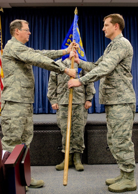 Col. Robert Hamm (left), commander of the 123rd Operations group, hands the 123rd Operations Support Squadron's new guidon to Lt. Col. Matthew Groves, squadron commander, during a redesignation ceremony at the Kentucky Air National Guard Base in Louisville, Ky., Nov. 24, 2013. Prior to the ceremony, the 123rd Operations Support Squadron was classified as a flight. (U.S. Air National Guard photo by Airman 1st Class Joshua Horton)