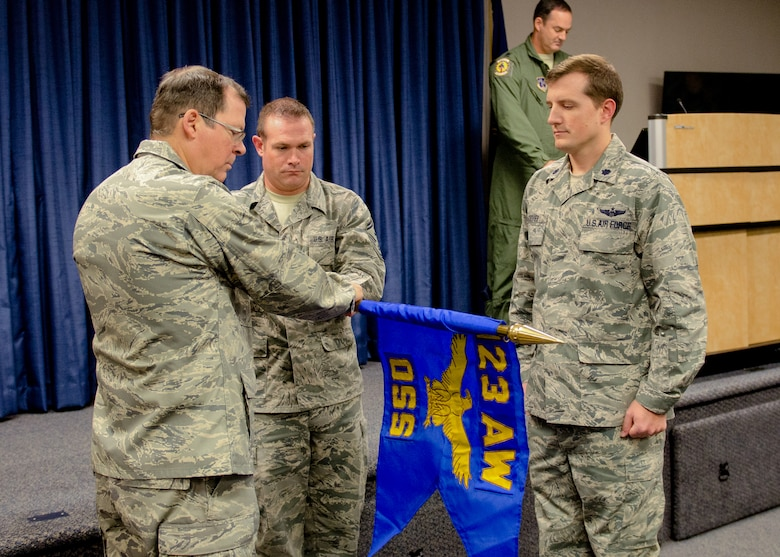 Col. Robert Hamm (left), commander of the 123rd Operations Group, and Senior Master Sgt. Colin King (center), operations group first sergeant, unfurl the new unit flag of the 123rd Operations Support Squadron as Lt. Col. Matthew Groves, 123rd OSS commander, stands by to accept the guidon during a redesignation ceremony at the Kentucky Air National Guard Base in Louisville, Ky., Nov. 24, 2013. Prior to the ceremony, the 123rd Operations Support Squadron was classified as a flight. (U.S. Air National Guard photo by Airman 1st Class Joshua Horton)