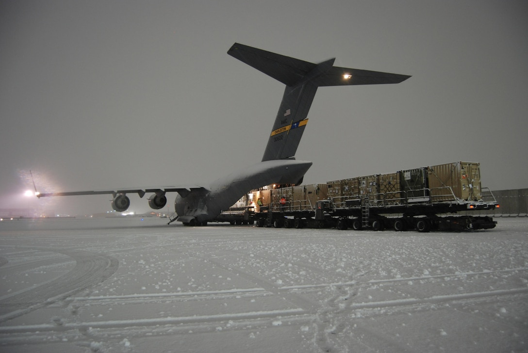 Airmen from the 455th Expeditionary Aerial Port Squadron load a C-17 Globemaster III Dec. 29, 2013, at Bagram Airfield, Afghanistan. The aircrew and aerial port Airmen downloaded and uploaded vehicles and cargo during the snowstorm. (U.S. Air Force photo/Capt. Brian Wagner)
