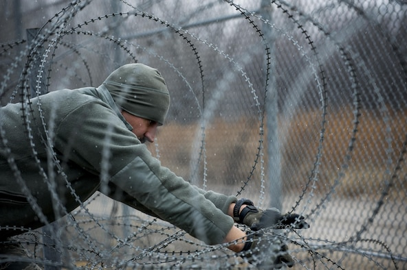 Staff Sgt. Adam Ross performs maintenance on concertina wire Dec. 12, 2013, at Transit Center at Manas, Kyrgyzstan. Concertina wire has razor-sharp edges, placed in coils as a barrier to deter anyone trying to breach a perimeter. Ross is a 376th Expeditionary Security Forces Squadron patrolman. (U.S. Air Force photo/Senior Airman George Goslin)