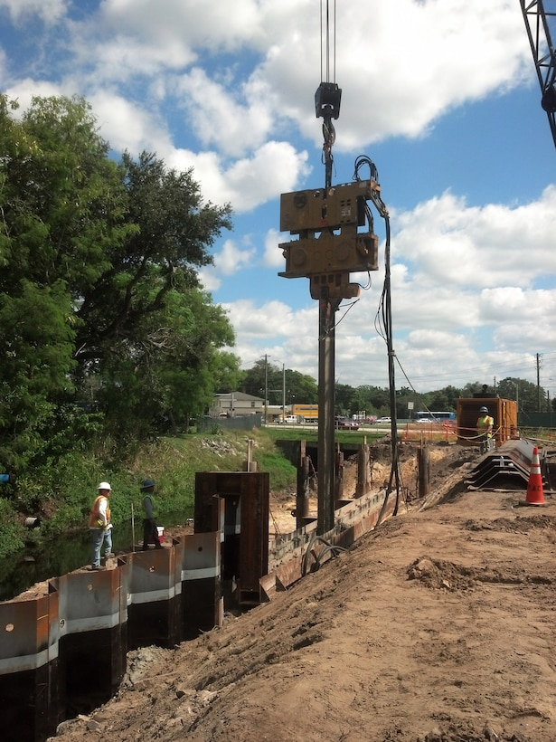 At the Wares Creek Flood Control Project in Bradenton, Fla., crews prepare for the installation of sheet pile, using a chisel beam to penetrate the dense limestone layer below. Each of three phases of the project was awarded to an 8(a) small business firm.