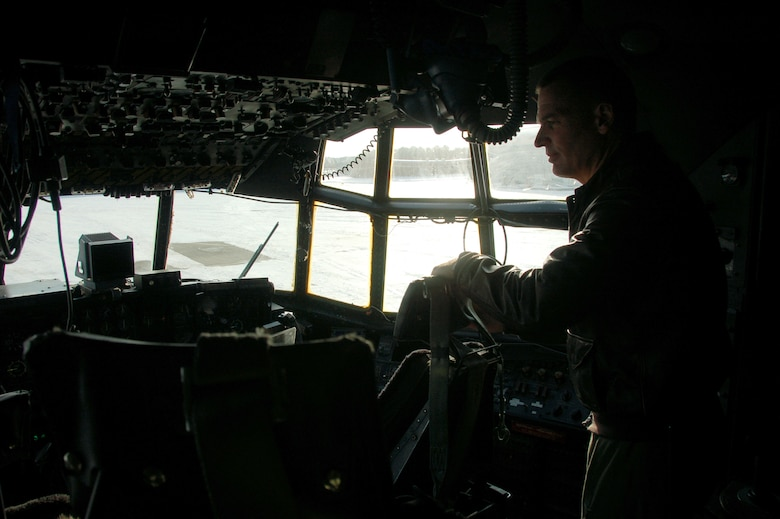 Col. Frank Detorie, commander of the 103rd Airlift Wing, peers out the window of a C-130H Hercules aircraft Dec. 19, 2013, on the ramp at Bradley Air National Guard Base, East Granby, Conn., as he waits for the inbound aircrew scheduled to launch the first locally-generated sortie with the unit's new airframe. (U.S. Air National Guard photo by Maj. Bryon Turner)
