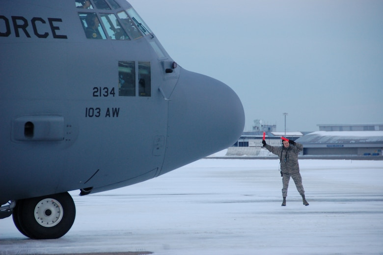 Master Sgt. Jon Favreau, a crew chief assigned to the 103rd Maintenance Group, guides a C-130H Hercules aircraft assigned to the 103rd Airlift Wing toward the runway moments before the first locally-generated sortie with the unit's new airframe at Bradley Air National Guard Base, East Granby, Conn., Dec. 19, 2013.  The aircrew was comprised of Airmen from the Connecticut Air National Guard, the New York Air National Guard and the U.S.A.F.  (U.S. Air National Guard photo by Maj. Bryon Turner)