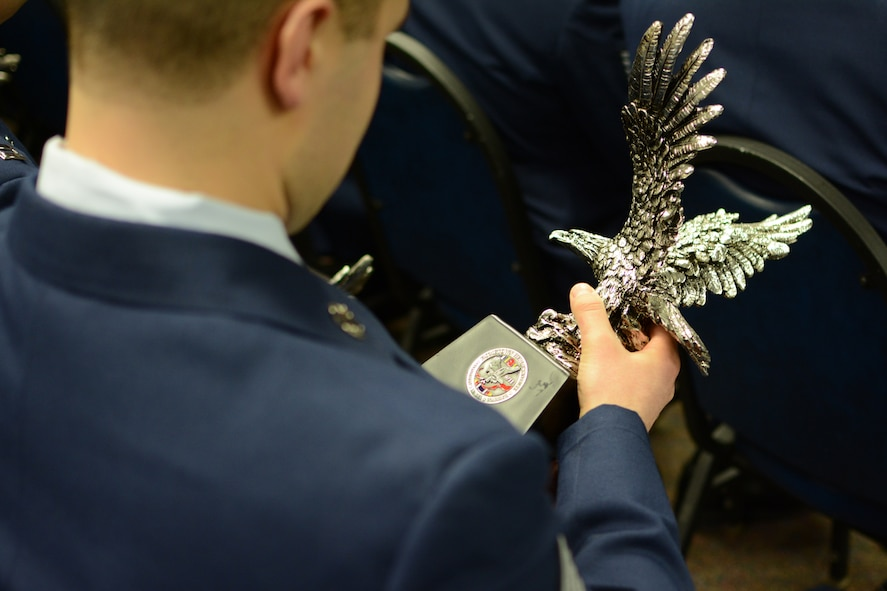 An Airman admires the award he received during a Hometown Hero Awards ceremony at Volk Field Combat Readiness Training Center, Volk Field, Wis., Jan. 4.  Recognition was given to more than 90 Airmen for their support during Operation Noble Eagle, Operation Enduring Freedom and Operation Iraqi Freedom. (Air National Guard photo by Senior Airman Andrea F. Liechti)