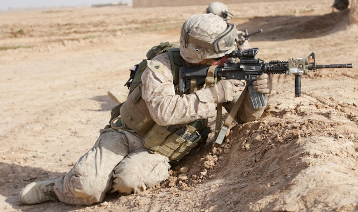 U.S. Marine Sgt. Brian Early, a squad leader with 1st Battalion, 9th Marine Regiment, looks through his rifle's scope to provide security for Marines moving to the next compound during a patrol in Helmand province, Afghanistan, Dec. 22. (U.S. Marine Corps photo by Cpl. Austin Long)