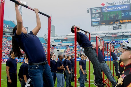 JACKSONVILLE, FLA. – Marine Recruiters from Recruiting Stations Jacksonville watch as future Marines compete in a pull up challenge at the end of the first quarter of the 2014 Gator Bowl on EverBank Field here, Jan. 1, 2014. The Marines conducted the pull-up challenge on the field to highlight the Esprit de Corps and physical fitness required of all Marines. The Marines of Recruiting Station Jacksonville had a large presence at the nationally televised football game showcasing the two rivals from the universities of Florida and Georgia. (Official Marine Corps photo by Lance Cpl. John-Paul Imbody)