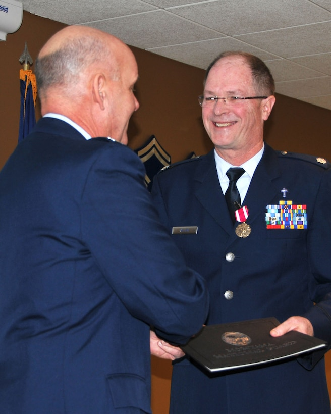 Chaplain (Lt. Col.) John Allen receives his certificate of retirement from the Armed Forces of the United States from 120th Fighter Wing Commander Col. J. Peter Hronek on Dec. 8, 2013 in Great Falls, Mont. National Guard photo/Senior Master Sgt. Eric Peterson.