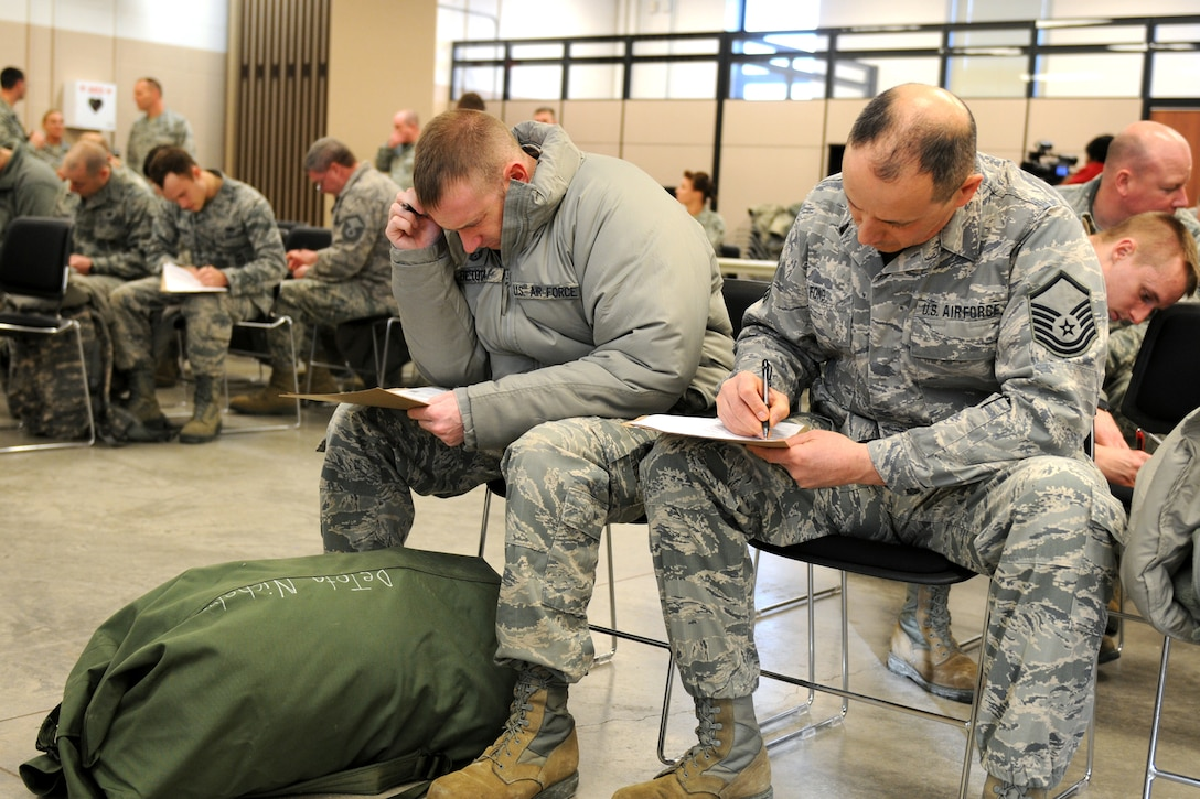 New York Air National Guard Tech. Sgt. Nicholas DeTota and New York Air National Guard Master Sgt. Bruce Fong along with others from the 174th Attack Wing fill out paperwork at Hancock Field in Syracuse, NY on 7 Jan 2014.  The unit members were volunteering to help support recovery efforts in Western NY as a result of the extreme cold and snow fall Monday and Tuesday.  (New York Air National Guard Photo by Tech. Sgt. Jeremy M. Call)