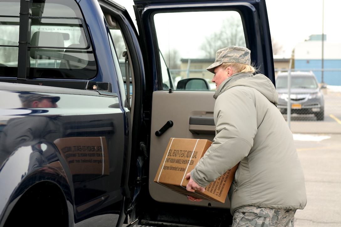 New York Air National Guard Staff Sgt. Christine Milback from the 174th Attack Wings Logistics Readiness Squadron loads a case of Meals Ready to Eat into a vehicle at Hancock Field in Syracuse, N.Y, Jan. 7, 2014. The vehicle was one of five that were used by volunteers from Hancock Field to support response efforts due to extreme cold and snow fall in Central NY. Each vehicle received a box of MREs as well as an emergency roadside kit, two shovels, reflective vests and a first aid kit. (New York Air National Guard photo by Tech. Sgt. Jeremy M. Call)