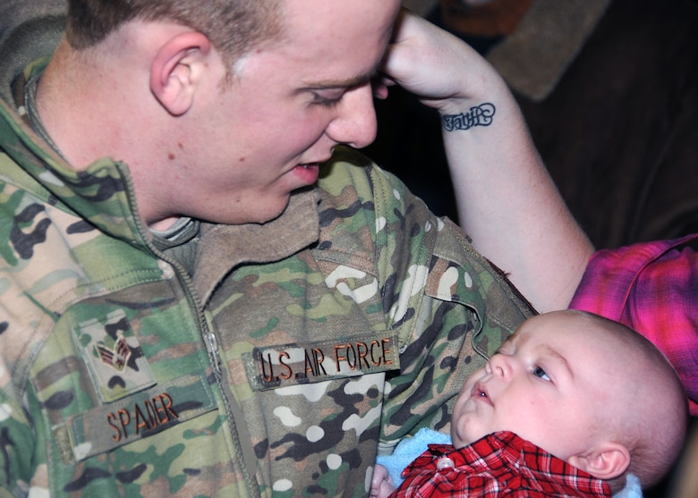 Airman First Class Dalton Spader meets his son Gavin for the first time upon return from a deployment to Kuwait. Gavin was born while Airman Spader was deployed. Airmen from the 143d Airlift Wing Operations Group, Maintenance Group and Logistics Readiness Squadron were deployed in support of Operation Enduring Freedom. National Guard Photo by Master Sgt John McDonald (RELEASED)