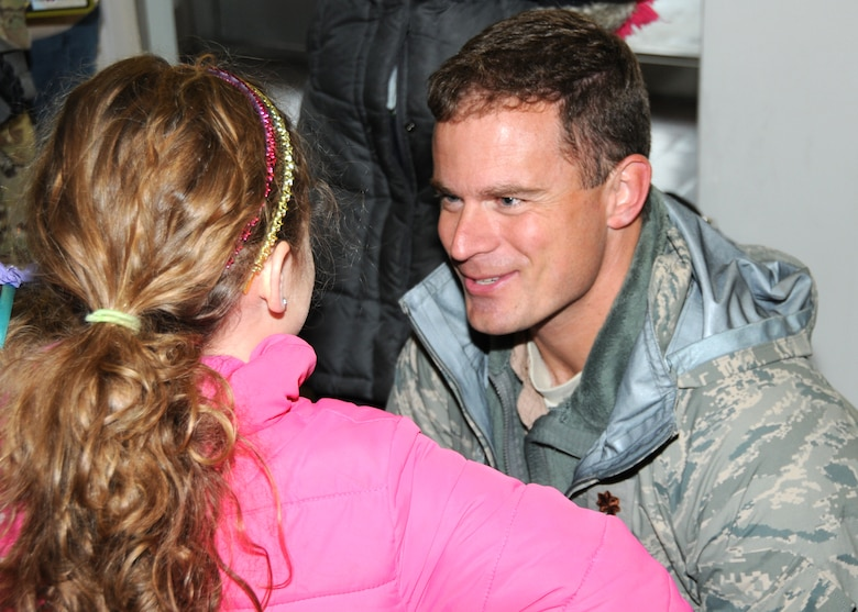 Major Mike Collins is greeted by his daughter upon return from a deployment to Kuwait. Airmen from the 143d Airlift Wing Operations Group, Maintenance Group and Logistics Readiness Squadron were deployed in support of Operation Enduring Freedom. National Guard Photo by Master Sgt John McDonald (RELEASED)