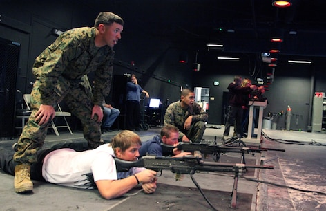 Two Morongo Unified School District seniors learn firing techniques from Provost Marshal's Office Marines during the Combat Center's annual Job Shadow day. The program pairs local students with Marines, sailors and civilian employees who work in their field of interest.