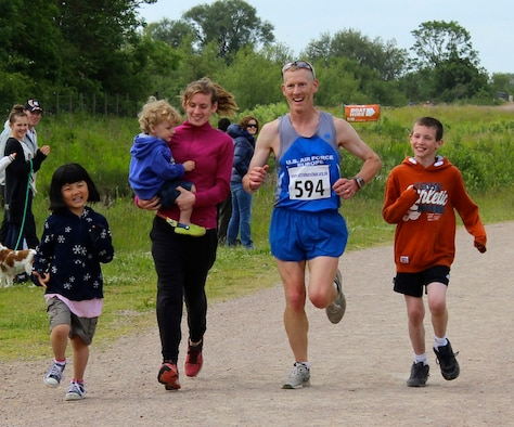 Lt. Col. Chris Bennett, second from right, prepares to cross the finish line of the Alexander the Great half-marathon on Father's Day, June 16, 2013, at Stanwick Lakes, Northamptonshire, England. As part of a family tradition, Bennett's children (from left to right) Emma, Ashton, Katie Reed and Elijah run with their dad every Father's Day. Bennett is the chief of airlift and tanker requirements (Courtesy photo/Molly Bennett)