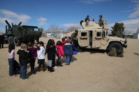 Joshua Tree Elementary School students line up to inspect tactical vehicles brought to their campus by Marine Wing Support Squadron 374 for a static display. Combat Center personnel set up static displays at a variety of community events throughout the year.