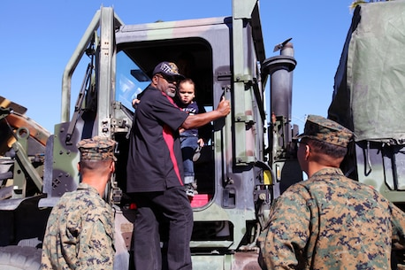Retired Marine Dwight Garner and his grandson, Maverick Burkleo, talk to Combat Logistics Battalion 7 Marines about their 7-ton vehicle during the Veterans Day celebration in Twentynine Palms. Combat Center personnel set up static displays at a variety of community events throughout the year.