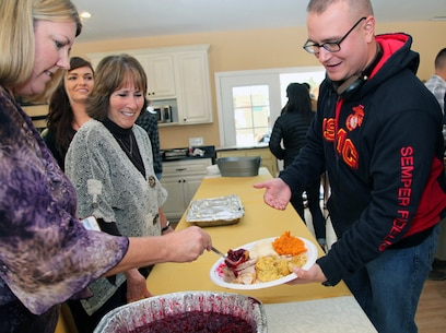Volunteers Meredith Plummer, left, and Marsha Cole top off Pfc. James Coleman's plate with cranberry sauce during Roughley Manor Bed and Breakfast's annual Thanksgiving dinner for Combat Center personnel.