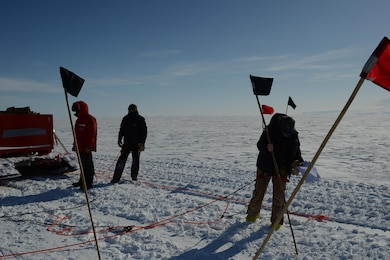 On right, ERDC Cold Regions Research and Engineering Laboratory's Dr. Zoe Courville marks a crevasse snow bridge for blasting while on a recent Antarctic traverse to refuel the South Pole Station.
