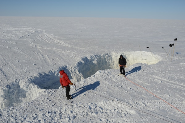 ERDC Cold Regions Research and Engineering Laboratory researchers on a recent Antarctic traverse, stand by a just blasted open crevasse. The open crevasse will be filled with snow and left safe to travel over.