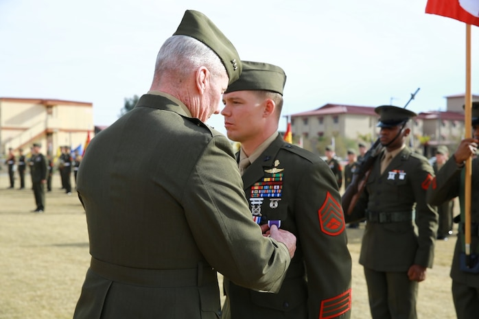 Lieutenant Gen. John Toolan, commanding general of I Marine Expeditionary Force, pins the Purple Heart on Staff Sgt. Timothy Williams, a section leader with 1st Reconnaissance Battalion, during an award ceremony when he received the Silver Star Medal and Purple Heart at Camp Las Flores, Marine Corps Base Camp Pendleton, Calif., Jan. 7, 2014. Williams, a native of Hudson, Mich., was recognized for his heroic actions in Afghanistan when he maintained a tactical advantage while being ambushed by a larger enemy force. Williams helped save the lives of multiple Marines and destroyed several enemy positions during the 10 hour attack. (U.S Marine Corps photo by Lance Cpl. Jonathan Boynes/released)
