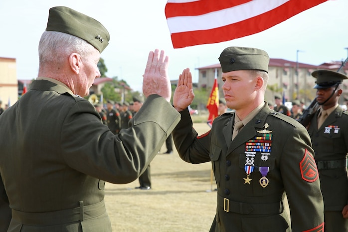 Lieutenant Gen. John Toolan, commanding general of I Marine Expeditionary Force, oversees the reenlistment of Staff Sgt. Timothy Williams, a section leader with 1st Reconnaissance Battalion, during an award ceremony held at Camp Las Flores, Marine Corps Base Camp Pendleton Calif., Jan. 7, 2014. Williams, a native of Hudson, Mich., was awarded the Silver Star Medal and Purple Heart for his heroic actions in Afghanistan when he maintained a tactical advantage while being ambushed by a larger enemy force. Williams helped save the lives of multiple Marines and destroyed several enemy positions during the 10 hour attack. (U.S Marine Corps photo by Lance Cpl. Jonathan Boynes/released)