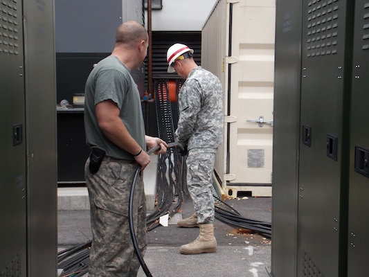 The 249th Engineer Battalion feeding cable through an access hole.