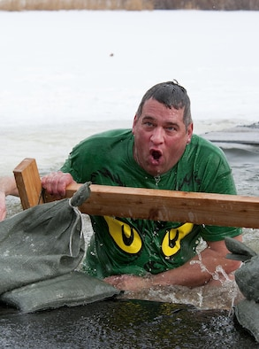Gene Duran scrambles to get out of the icy waters of Sloan Lake, Cheyenne, Wyo., during the second annual Matthew S. Schwartz Memorial Polar Plunge Jan. 4, 2014. Participants braved 16-degree air and 30-degree water temperatures to raise money for a foundation which helps wounded explosive ordnance technicians and their families. Duran is the 90th Civil Engineer Squadron unit deployment manager. (U.S. Air Force photo/R.J. Oriez)