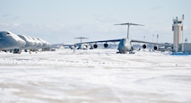 Team Dover aircraft maintenance personnel tow a C-5M Super Galaxy down the flight line Jan. 3, 2014, at Dover Air Force Base, Del. Snow removal crews from the 436th Civil Engineer Squadron cleared the flight line during and after the snow storm. (U.S. Air Force photo/Roland Balik)
