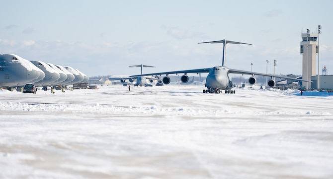 Aircraft maintenance personnel tow a C-5M Super Galaxy down the flightline Jan. 3, 2014, at Dover Air Force Base, Del. Snow removal crews from the 436th Civil Engineer Squadron cleared the flightline during and after a recent snow storm. (U.S. Air Force photo/Roland Balik)