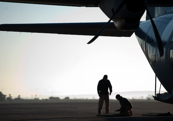 Airman 1st Class Andrew Bracamontes, left, and Senior Airman Matthew Howard  double check equipment prior to boarding a C-130J Hercules, Dec. 18, 2013, at Sigonella Naval Air Station, Italy. Fly-away security team members provided security for the Airmen of the 37th Airlift Squadron during a mission to Central African Republic, Africa. The 37th AS delivered much-needed supplies and personnel as part of a peace-keeping mission to support the civilian population disrupted by the nation's recent conflicts. Bracamontes and Howard are FAST members assigned to Ramstein Air Base, Germany. (U.S. Air Force photo/Senior Airman Damon Kasberg)