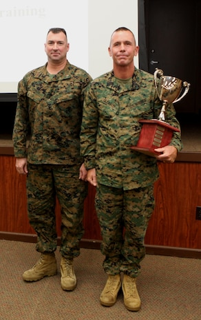 Chief Warrant Officer 3 Michael J. Smith (Left), band officer, U.S. Marine Corps Forces, Pacific Band, and Master Gunnery Sgt. Mark D. Gleason, bandmaster, stand with the 2013 Marine Corps Band of the Year Award. The MarForPac Band received the award for the first time.